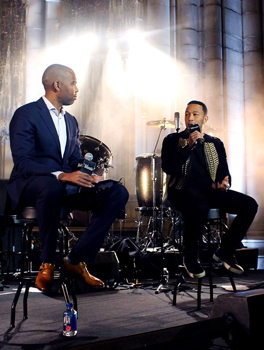Singer John Legend sitting on stage talking into a microphone with host